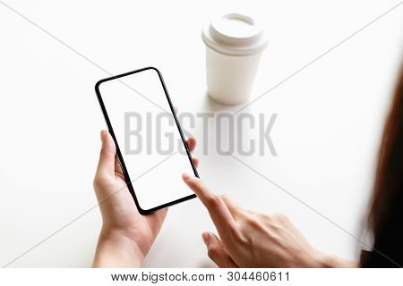 Woman Holding Smartphone Mockup Of Blank Screen On The Table.