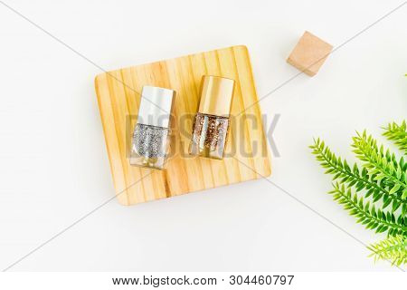 Nail Polish Of Beautiful Colorful On Wood Platform And White Background.