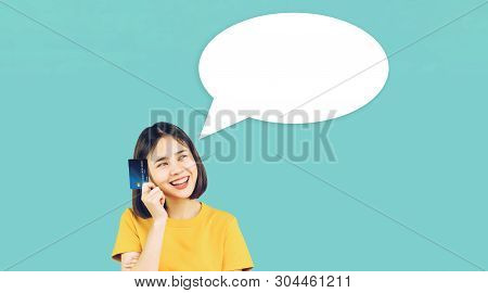 Asian Woman Yellow Casual Clothes Holding Credit Card On Light Blue Background With Speech Bubble Fo