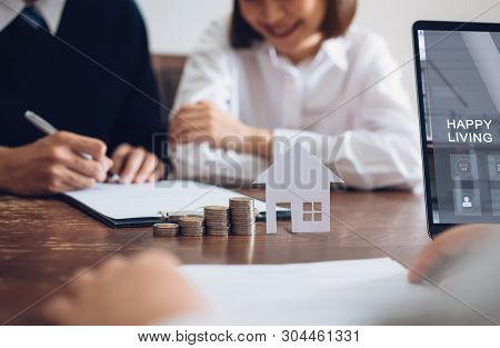 Couples Signed A Contract To Buy A House From The Broker. Coin To Stack Money And Model House Placed