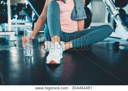 Close-Up Woman Hand is Exercised in Fitness Club, Sporty Woman is Resting After Working Out Jogging on Treadmill Machine While Dinking a Bottle of Water in Gym., Sport Club and Healthy Concept.