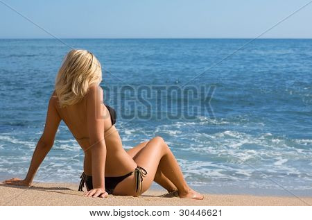 Sexy girl in bikini on a sandy beach.