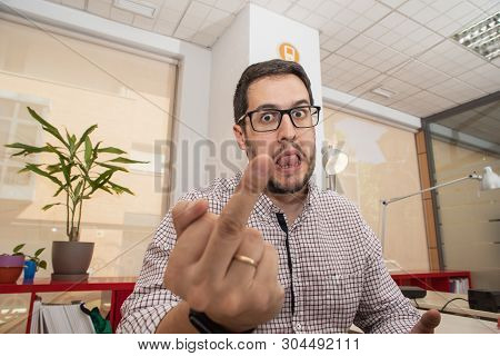 Young Man With Glasses In The Office Staring, In An Agressive Posture
