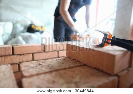 Focus On Construction Site Made Of Red Bricks And Concrete. Professional Engineer Stacking Special E