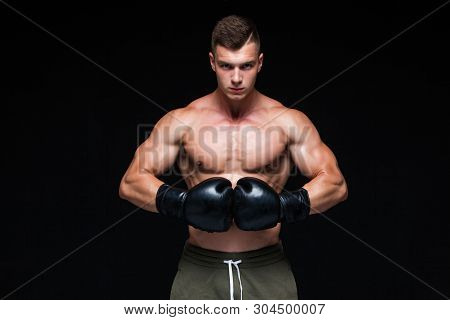Muscular Young Man In Black Boxing Gloves And Shorts Shows The Different Movements And Strikes In Th