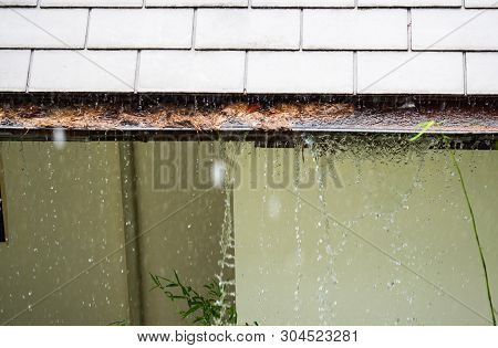 Close Up View On Clogged Rain Gutter In The Rain. Home Guttering, Gutters