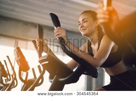 Young People - Group Of Women And Men - Doing Sport Biking In The Gym For Fitness. Young Woman Worko