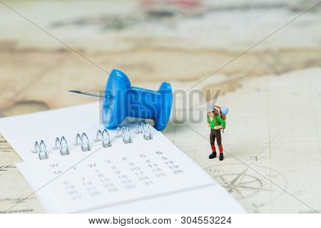 Travel, tourism, vacation or wanderlust life concept, miniature young man backpacker standing on vintage world map with compass, pushpin and calendar plan for next destination, new adventure journey. poster