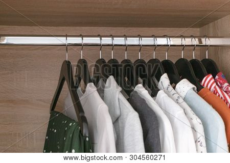 Female Different Clothes On Black Wooden Hang In Wardrobe Closet