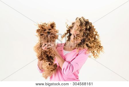 Happy Woman With Long Curly Hair Holds Small Dog. Beautiful Girl Hugs Little Dog. Lady With Puppy. S