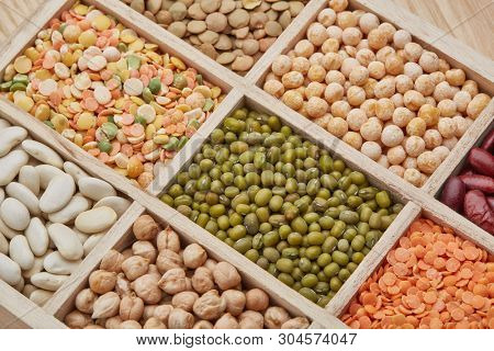 Background from various kinds legumes. Different varieties of legumes in a wooden box. Dry haricots, lentils, peas, chickpeas, mung beans.  Top view.