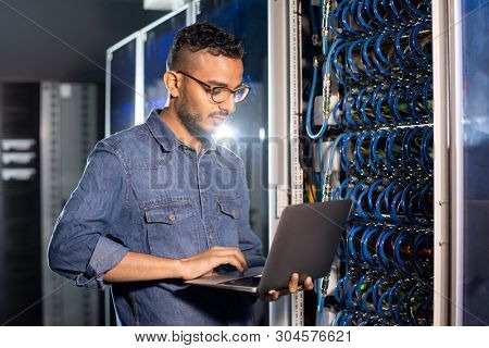 Serious busy young Arabian server engineer with beard standing in database server room and using laptop while examining work of supercomputer