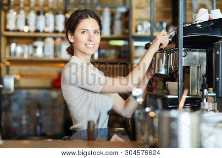 Young successful self-employed barista in workwear standing by coffee machine while making cappuccino or espresso for clients