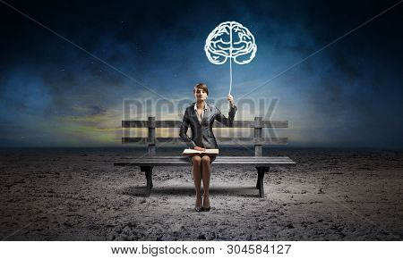 Young Woman With Open Book Sitting On Wooden Bench Outdoor. Brainstorming And Idea Generation. Beaut