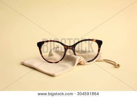 Modern fashionable acetate spectacles, torture color with textile beige bag laying on light yellow background. poster