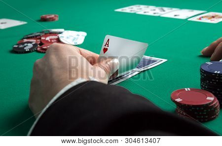 Poker Table During A Game. Four Aces Cards Holding In Hand. Chips And Cards On The Table.