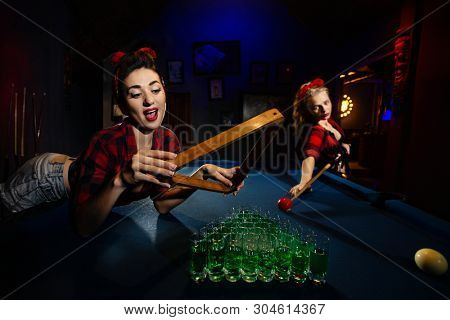 Two young  pin-up Females Shooting Billiards with stemwares instead of billiard balls