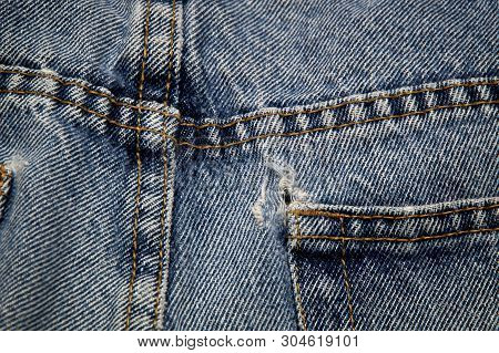 Top View Of Worn Out Double Sewn Seams And Frayed Hole On Pocket Of Old Blue Jeans,
