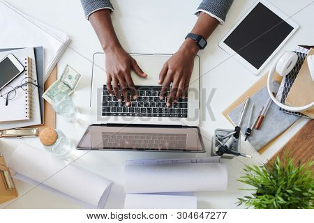 Hands of young mixed-race employee or student over laptop keypad during work over new design or business project by desk