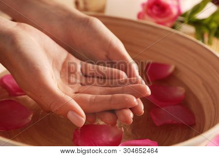 Woman soaking her hands in bowl of water and petals, closeup with space for text. Spa treatment poster