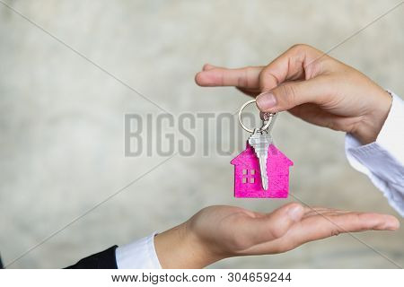 Real Estate Agent Holding House Key To His Client After Signing Contract Agreement In Office,concept