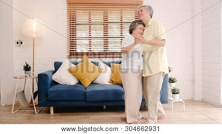 Asian Elderly Couple Dancing Together While Listen To Music In Living Room At Home, Sweet Couple Enj