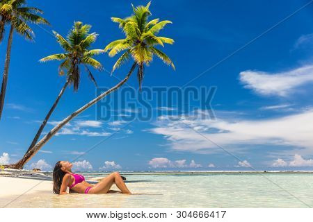 Beach vacation paradise suntan woman relaxing lying down sun tanning in tropical idyllic summer background in Caribbean with blue sky and palm trees.