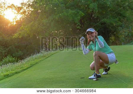 Sport Healthy. Golfing Game. Asian Woman Golfer Action To Win After Long Putting Golf Ball On The Gr