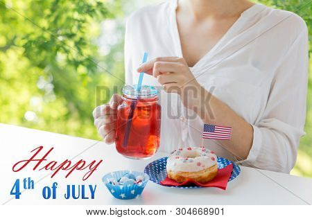 independence day, celebration and holidays concept - close up of woman with glazed sweet donut, candies and juice in glass mason jar or mug at 4th july party over green natural background