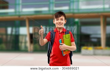 education and people concept - smiling little student boy in red polo t-shirt in glasses with books and bag showing thumbs up over school yard background