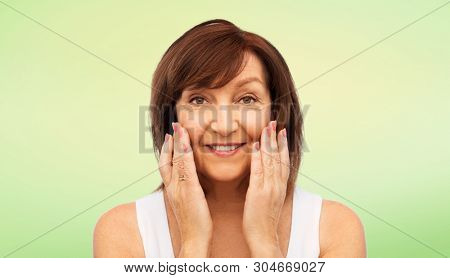beauty, skin care and old people concept - portrait of smiling senior woman touching her face over lime green background