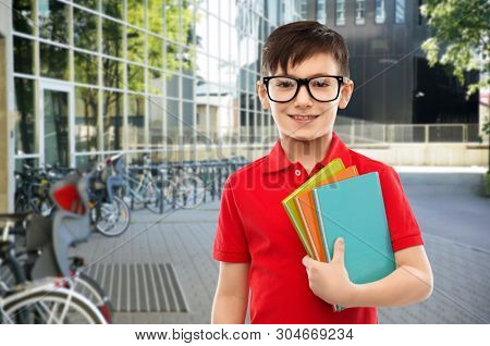 education and people concept - portrait of smiling little student boy in red polo t-shirt in glasses with books over school yard background