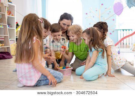Preschool Teacher Plays With Group Of Kids Sitting On A Floor At Kindergarten