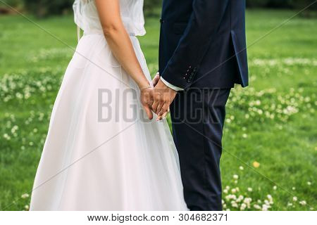 Hands Of Bride And Groom. New Young Couple Holding Hands After Their Wedding. Young Married Couple H