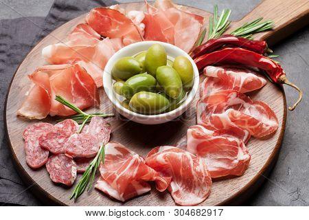 Traditional spanish jamon, prosciutto crudo, italian salami, parma ham. Antipasto plate and olives