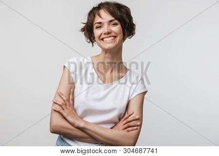 Image of cheerful woman in basic t-shirt smiling at camera while standing with arms crossed isolated over white background