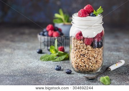 Granola Parfait With Yogurt, Oat Granola, Fresh Berries, Honey And Mint Leaves In Tall Glass Jar, Co