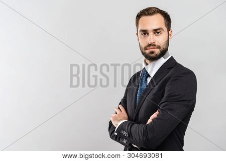 Attractive young businessman wearing suit standing isolated over gray background, arms folded