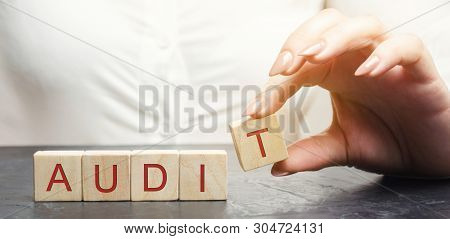 A Woman Puts Wooden Blocks With The Word Audit. Inspection Of Financial And Economic Activities Of I