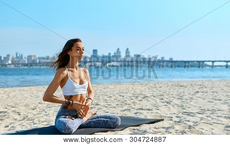Portrait Of Young Woman Relaxing Practicing Yoga And Meditation On The Sand Beach With City Backgrou
