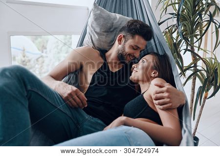 He Will Never Let Her Go. Beautiful Young Couple Embracing And Smiling While Resting In The Hammock
