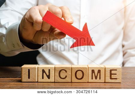 A Businessman Is Holding A Red Down Over The Words Income. Fall Profits, High Costs And Corpor Press