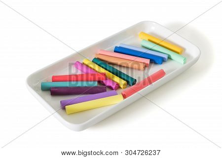 Colored Chalk Pastels In A Beautiful White Plate Isolated On White Background