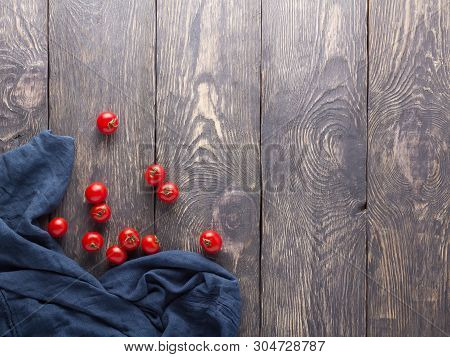 Small Cherry Tomatoes, Blue Napkin On Wooden Background