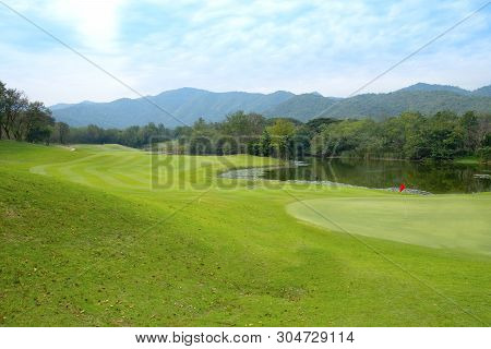 Golf Course Landscape With Clear Sky, Mountains And Trees