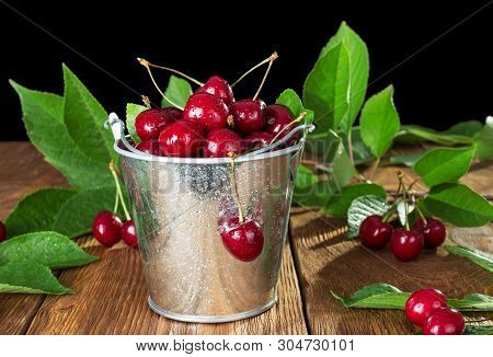 Juicy Cherries In A Bucket In The Water Droplets On Wooden Table Isolated On Black Background