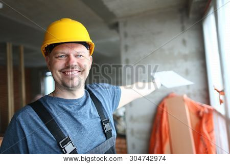 Portrait of hardworking man looking at camera joyfully. Smart constructor in protective outfit and hardhat showing something with paper tablet. Building concept poster