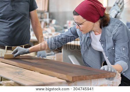 Middle-aged Craftswoman Working In Woodworking Workshop. Female Varnishing Wooden Board With Oil, Va