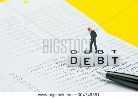 Debt, Financial Obligation Or Money To Pay Back To Creditor Concept, Miniature Businessman Standing