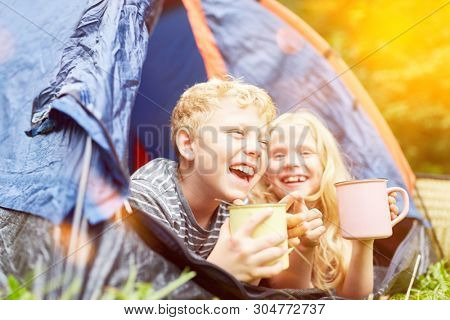 Two happy children are camping together in the tent in summer